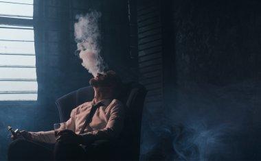 Man in room smoking cigarette